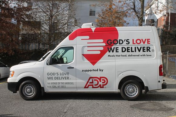 ADP van with God's Love logo in front of a tree and a house